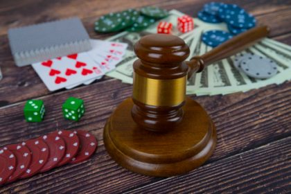 judge gavel and set of playing cards with dices, money and chips, on wooden table