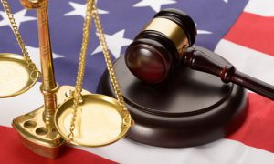 Justice Scale And Wooden Brown Gavel On Usa Flag