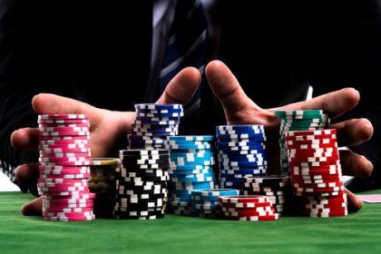 Gambler man hands pushing large stack of colored poker chips